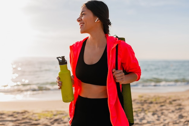 핑크 윈드 재킷을 입고 이어폰에서 음악을 듣고, 요가 매트와 물 한 병, 건강한 라이프 스타일을 들고 바다 해변에서 아침 일출에 스포츠를하는 젊은 매력적인 웃는 여자
