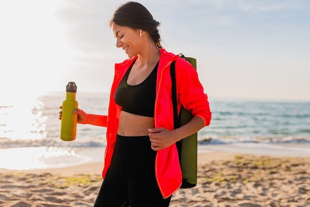 ヨガマットと水のボトルを保持し、健康的なライフスタイル、イヤホンで音楽を聴き、ピンクのウインドブレーカージャケットを着て海のビーチで朝の日の出でスポーツをしている若い魅力的な笑顔の女性