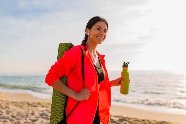 Молодая привлекательная улыбающаяся женщина занимается спортом в утреннем восходе солнца на морском пляже, держа коврик для йоги и бутылку воды, здоровый образ жизни, слушает музыку в наушниках, носит розовую ветровку