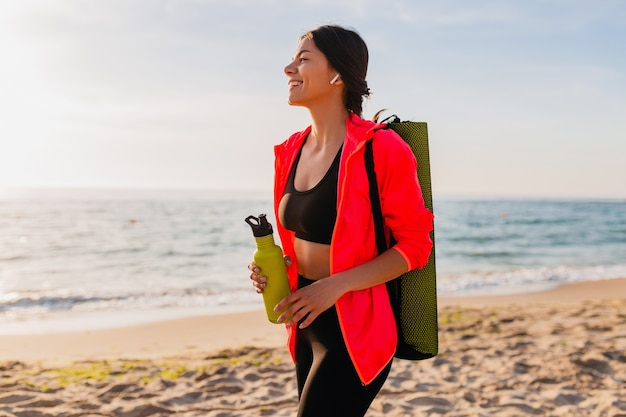 Young attractive smiling woman doing sports in morning sunrise on sea beach holding yoga mat and bottle of water, healthy lifestyle, listening to music on earphones, wearing pink windbreaker jacket