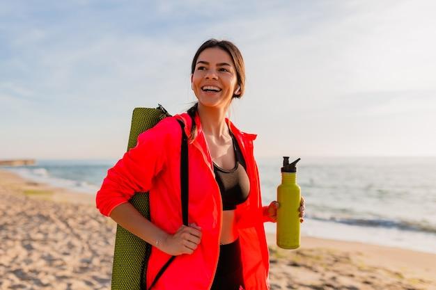Giovane donna sorridente attraente che fa sport all'alba di mattina sulla spiaggia del mare che tiene stuoia di yoga e bottiglia di acqua, stile di vita sano, ascolto di musica sugli auricolari, giacca a vento rosa da indossare