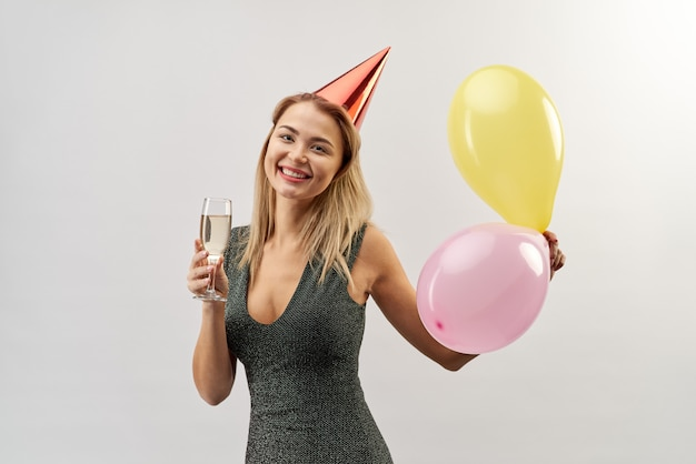 Young attractive smiling woman dressed in a dress with a glass of champagne, festive cap on her head and balloons in hand