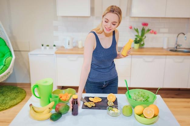 Молодая привлекательная усмехаясь женщина держит свежие пить вытрезвителя в бутылках пока варящ свежие фрукты и салат в кухне. диета детокс. здоровая пища. здоровое питание