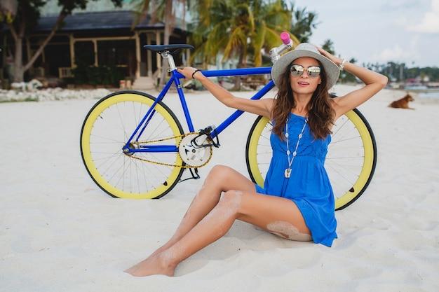 帽子とサングラスを身に着けている自転車と熱帯のビーチの砂の上に座っている青いドレスの若い魅力的な笑顔の女性