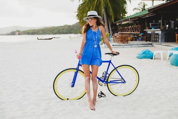 Молодая привлекательная улыбающаяся женщина в синем платье гуляет по тропическому пляжу с велосипедом в шляпе и солнцезащитных очках