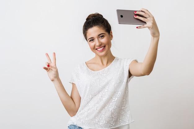スマートフォンを押し、ピースサイン、肯定的な感情を示す、selfie写真を作る白いブラウスの若い魅力的な笑顔の女性