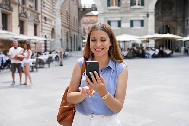 コミュニケーションにスマートフォンを使用して旧市街の広場で若い魅力的な笑顔の女性。いい感じ。現代の技術の利点。