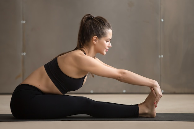 Young attractive smiling woman in paschimottanasana pose, grey s