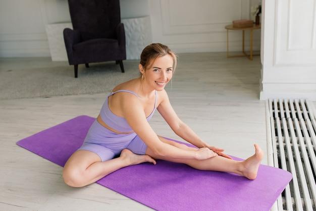 Молодая привлекательная улыбающаяся женщина занимается йогой, тренируется, носит спортивную одежду, бюстгальтер, домашнее обучение