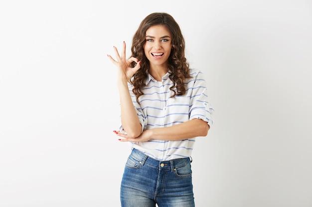 肯定的なジェスチャー、流行に敏感なスタイル、分離、巻き毛を示す若い魅力的な笑顔の女性