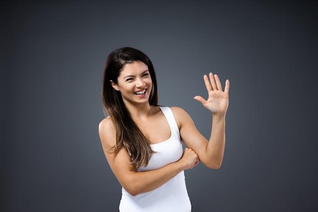 彼女の手のひらを立って見せている若い魅力的な笑顔の女性。彼女は誰かに手を振ったり挨拶したりしています。