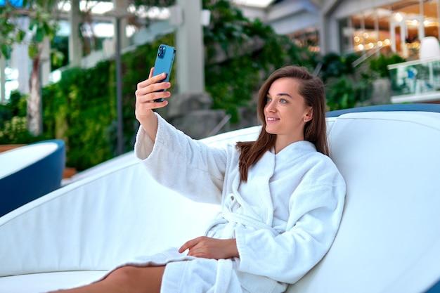 Молодая привлекательная улыбающаяся женщина в белом халате, делающая селфи портретную фотографию на камеру смартфона во время отдыха на спа-курорте