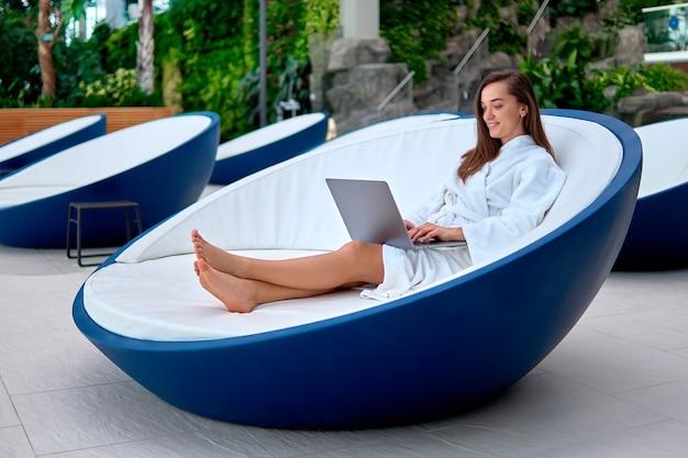 Молодая привлекательная улыбающаяся женщина в белом халате, использующая компьютер для просмотра видео и просмотра в интернете, лежа на шезлонге во время отдыха на спа-курорте