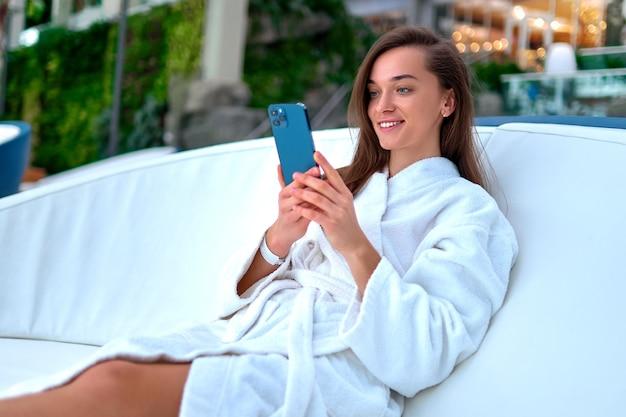 Молодая привлекательная улыбающаяся женщина в белом халате, использующая смартфон для просмотра видео и просмотра в интернете, лежа на шезлонге во время отдыха на спа-курорте