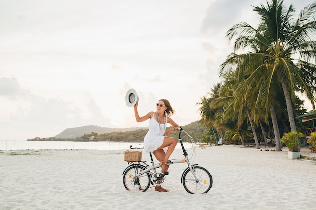 Young attractive smiling woman in white dress riding on tropical beach on bicycle wearing hat and sunglasses