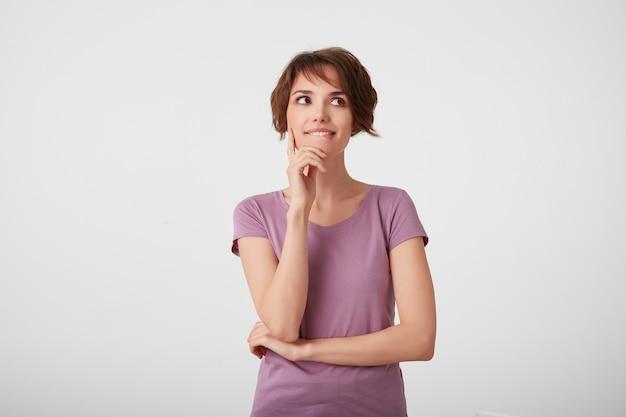 空白のtシャツを着た若い魅力的な笑顔の若い短い髪の女性は脇に見え、唇を噛み、考えています。白い背景の上に立っています。