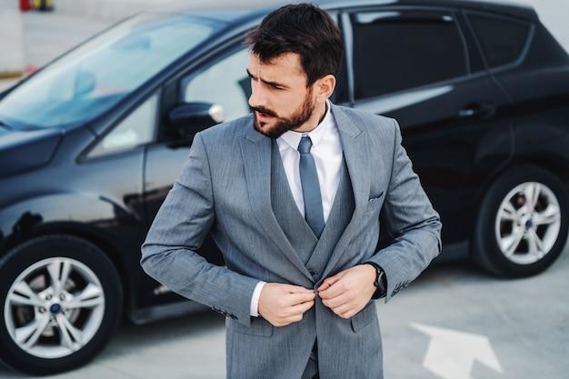 若い魅力的な洗練された白人ビジネスマンが彼のタキシードをボタンで留めます。背景には彼の高価な車があります。