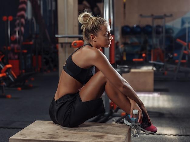 ジムでのトレーニングでセットの間休んでいるスポーツウェアの若い魅力的なスポーツ女性