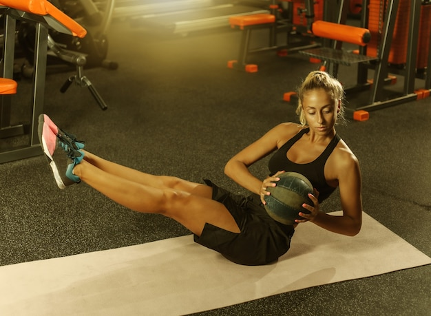 체육관에서 의학 공으로 운동복 훈련에 젊은 매력적인 스포츠 여자. 기능 훈련 개념