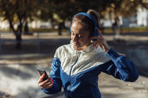 헤드폰 스포츠에서 젊은 매력적인 스포츠 여자 스포츠 공원에서 음악을 수신합니다.