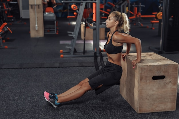 Young attractive sport woman in sportswear is practicing back push ups at wooden box in the gym. functional training concept