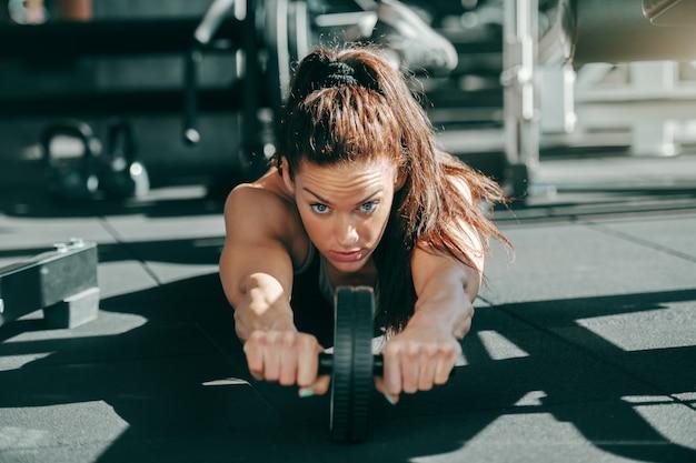 포니 테일 체육관 바닥에 복근 운동을 하 고 젊은 매력적인 스포티 한 여성 보디. 누군가의 말 때문에 포기하지 말고 더 강하게 밀어 붙이도록 동기를 부여하십시오.