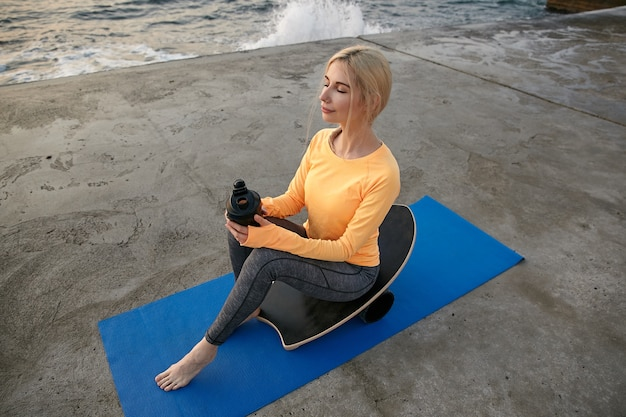 ブロンドの髪を持つ若い魅力的なスポーティな女性は、海辺でスポーツをし、バランスボードに座って、タンパク質とシェーカーを保持し、思慮深く脇を見て