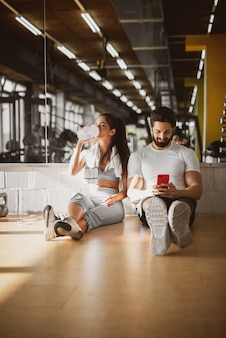 Young attractive sporty fitness couple sitting on the floor of the gym and making a break and relax time, leaning on the mirror with mobile and water.