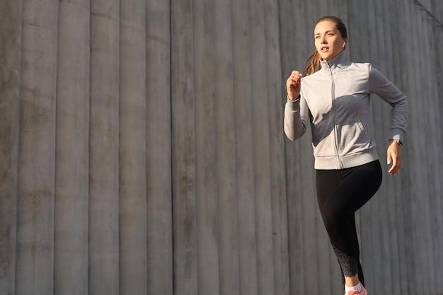 Молодая привлекательная спортивная женщина фитнеса, работающая на открытом воздухе на закате или восходе солнца в городе. Premium Фотографии