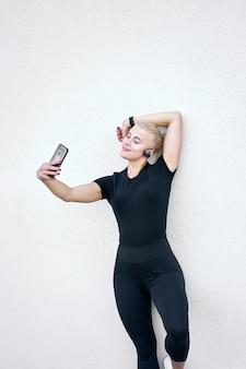 Молодая привлекательная спортивная девушка в черной спортивной одежде, слушающая музыку и принимающая селфи на фоне белой стены. концепция активного и здорового образа жизни.