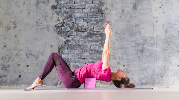 Young attractive sporty yogi woman practicing yoga using pink block