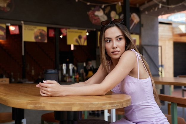 Young attractive stylish asian pretty girl sitting at dinery with cup of coffee