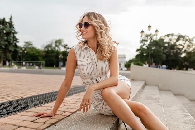 Giovane donna sorridente bionda elegante attraente che si siede nella via della città in vestito bianco da stile di modo di estate che indossa occhiali da sole, stile sexy ed elegante