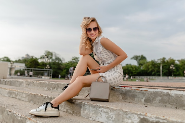 Young attractive stylish blonde woman sitting in city street in summer fashion style dress wearing sunglasses, purse, silvers sneakers