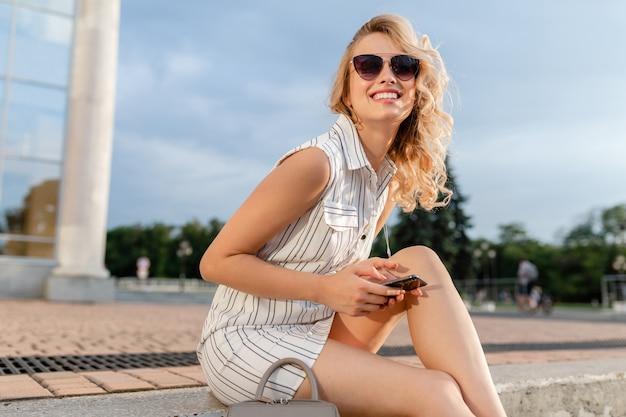 Молодая привлекательная стильная блондинка сидит на городской улице в летнем модном платье в солнечных очках, держит телефон и смеется откровенно