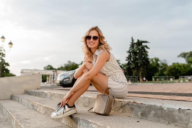 サングラス、財布、銀のスニーカーを身に着けている夏のファッションスタイルのドレスで街の通りに座っている若い魅力的なスタイリッシュなブロンドの女性