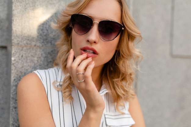 Giovane donna bionda alla moda attraente che cammina nella via della città in vestito da stile di modo di estate che indossa occhiali da sole, look sexy
