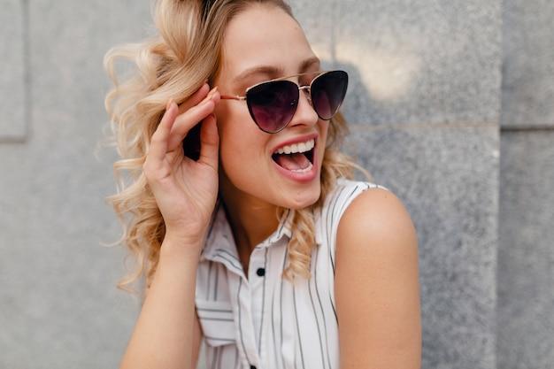 サングラスをかけた夏のファッションスタイルのドレスで街を歩いている若い魅力的なスタイリッシュなブロンドの女性、笑って驚いた