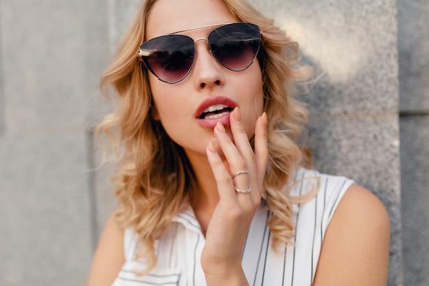 サングラスをかけて夏のファッションスタイルのドレスで街を歩く若い魅力的なスタイリッシュな金髪