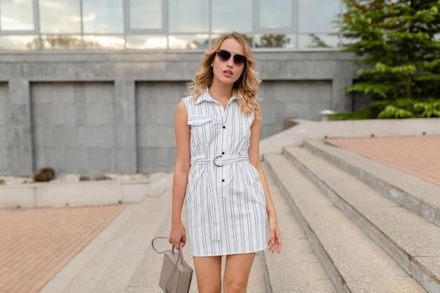 Giovane donna elegante elegante attraente con capelli biondi che cammina nella via della città in vestito bianco da portare degli occhiali da sole di stile di modo di estate