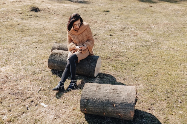 Молодая привлекательная стильная девушка на природе на фоне леса с телефоном в солнечный день