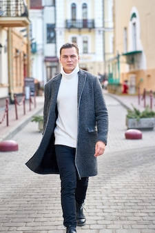 Young attractive stylish hipster man wearing a gray coat, white sweater and black jeans walking in the street