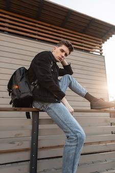 유행 청바지 옷에 젊은 매력적인 세련된 남자가 앉아서 나무 빈티지 건물 근처 밝은 봄 일몰을 즐깁니다.