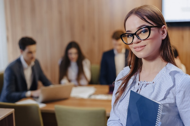 Young attractive stylish office worker girl in glasses with a notebook in the hands on background of working colleagues