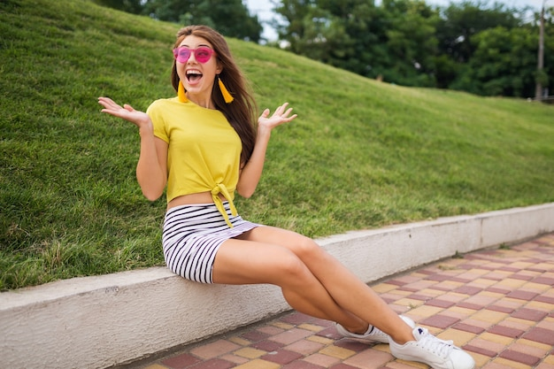 Young attractive stylish smiling woman having fun in city park, wearing yellow top, striped mini skirt, pink sunglasses, white sneakers, summer style fashion trend, sending kiss, flirting