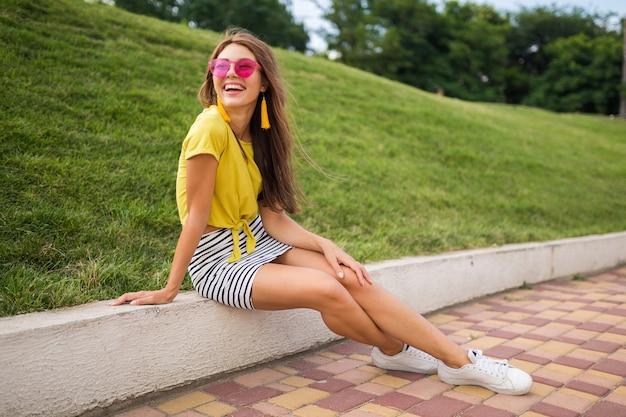 都市公園で楽しんでいる若い魅力的なスタイリッシュな笑顔の女性、ポジティブ、感情的、黄色のトップ、ストライプのミニスカート、ピンクのサングラス、白いスニーカー、夏のスタイルのファッショントレンド、長い脚を身に着けている