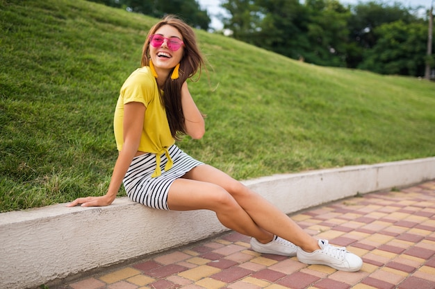 Молодая привлекательная стильная улыбающаяся женщина, развлекающаяся в городском парке, позитивная, эмоциональная, в желтом топе, полосатой мини-юбке, розовых солнцезащитных очках, белых кроссовках, тенденции моды в летнем стиле, длинные ноги