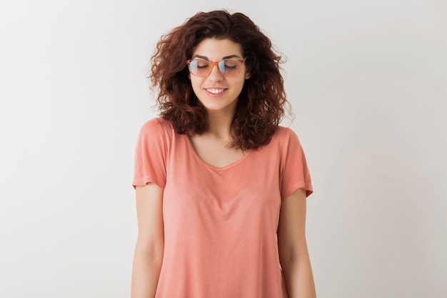 Young attractive stylish woman in glasses with closed eyes, thinking, dreamimg, curly hair, smiling, positive emotion, happy, isolated, pink t-shirt, student