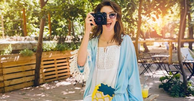 Молодая привлекательная стильная женщина в парке, уличный стиль, тренд летней моды, синий плащ, белое платье в стиле бохо, аксессуары, фотографирование на старинный фотоаппарат, улыбка, счастливые эмоции, солнечный