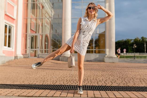 Giovane donna alla moda attraente che posa divertente in scarpe da ginnastica in strada della città in vestito da stile di moda estiva che indossa occhiali da sole e borsa